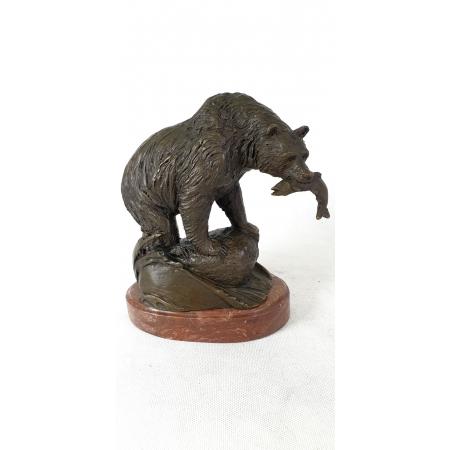 Медведь с рыбой на красном камне